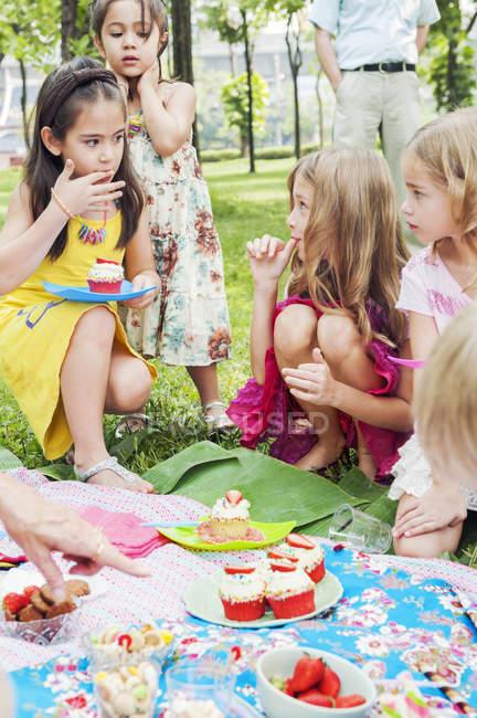 Діти, що веселяться в день народження пікнік, зосереджені на передньому плані — стокове фото