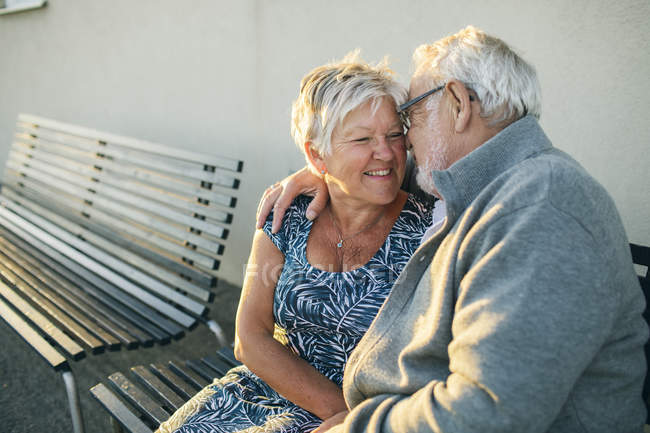 Senior couple hugging on bench, focus on foreground — Stock Photo