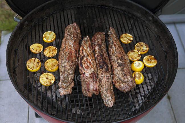 Tenderloin and lemons on grill, selective focus — Stock Photo