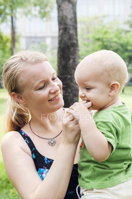 Mère nourrissant fils fraise, se concentrer sur le premier plan — Photo de stock