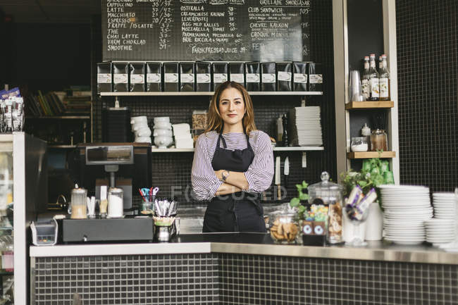 Portrait of barista looking at camera behind counter in cafe — Stock Photo
