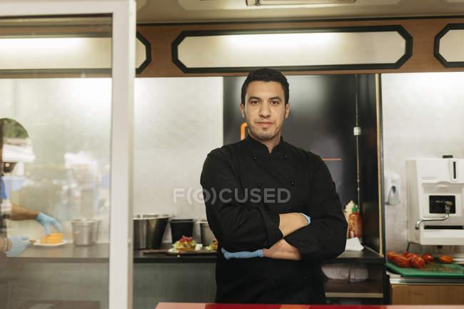 Chef che guarda la macchina fotografica nel camion del cibo, messa a fuoco selettiva — Foto stock