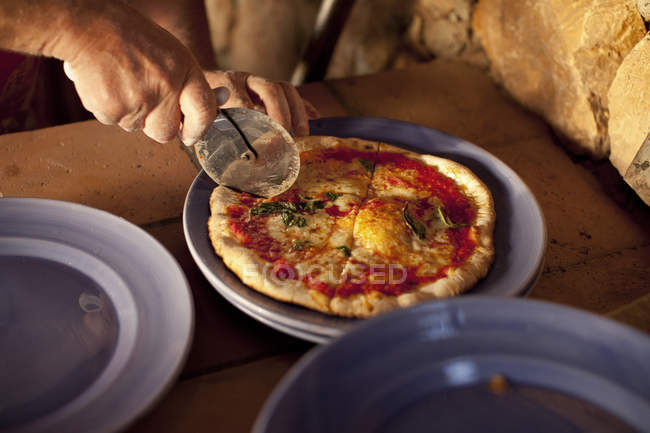 Female hands cutting pizza, selective focus — Stock Photo