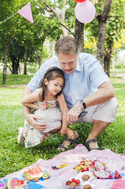 Vater und Tochter beim Geburtstagspicknick, Fokus im Vordergrund — Stockfoto