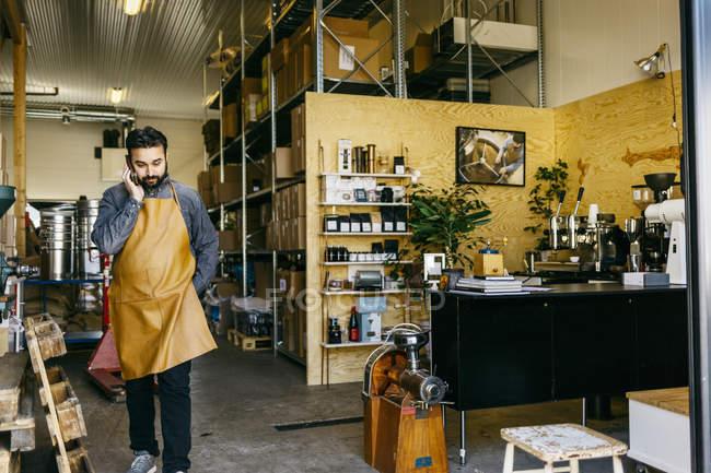 Piccolo imprenditore presso negozio di torrefazione caffè comunica sul cellulare — Foto stock