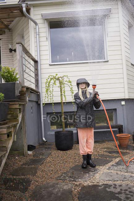 Девушка со шлангом против дома, избирательный фокус — стоковое фото