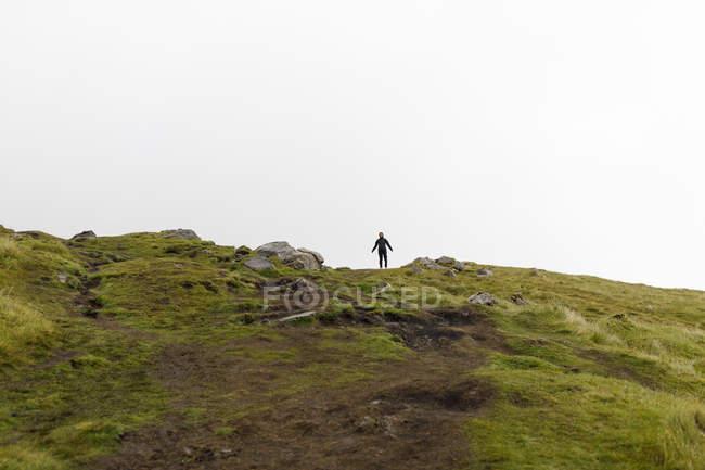 Vue panoramique sur la colline, femme debout en arrière-plan — Photo de stock