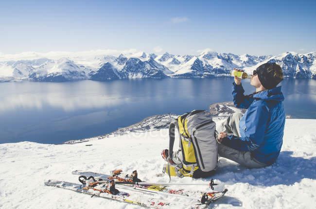 Side view of skier sitting on snow in Lyngen, Norway — стоковое фото