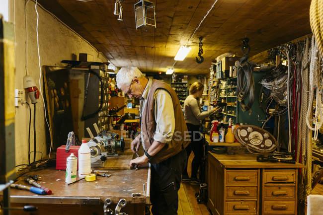 Fabbricante di corde in negozio, ragazza in sottofondo, messa a fuoco selettiva — Foto stock