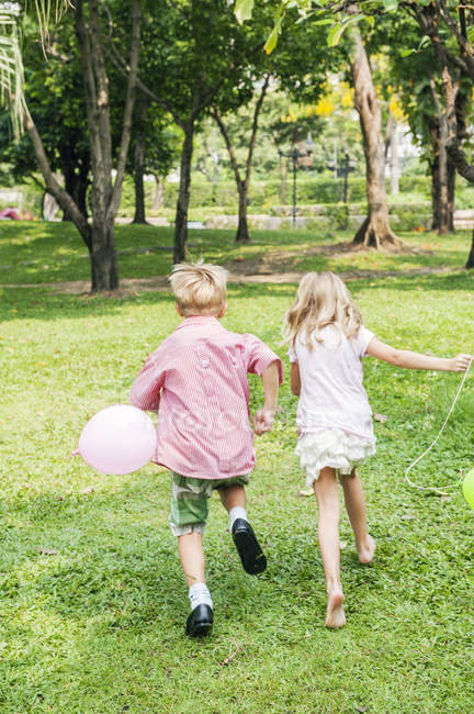 Rear view of children running with balloons in park — Stock Photo