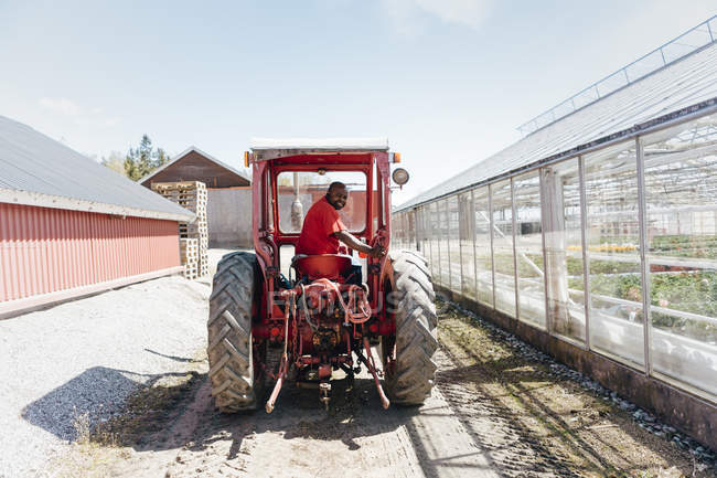 Garden centre worker on tractor, selective focus — Stock Photo