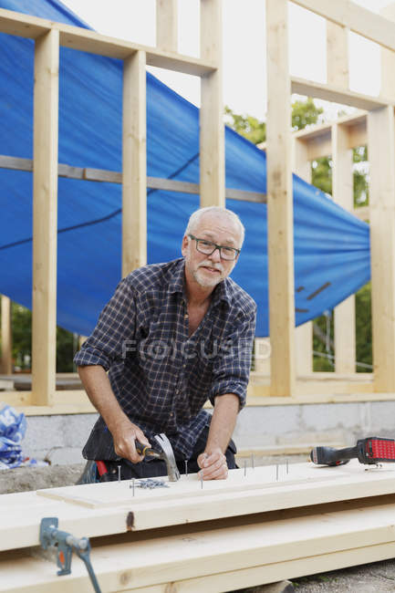 Carpenter hammering nail at construction site — Stock Photo
