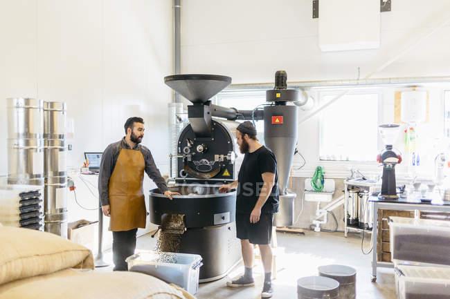 Deux hommes ayant la conversation contre la machine de torréfaction de café — Photo de stock