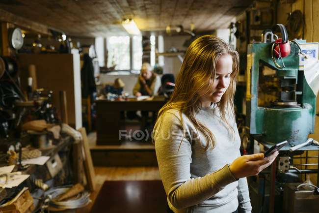 Teenage girl looking at phone in rope maker shop — Stock Photo