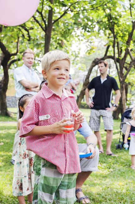 Junge hält Getränk beim Geburtstagspicknick — Stockfoto