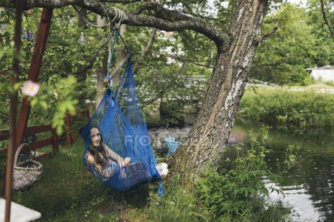 Девочка отдыхает в гамаке в шведском городе Фефорс — стоковое фото