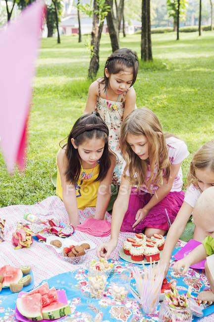 Children at birthday picnic, focus on foreground — стокове фото