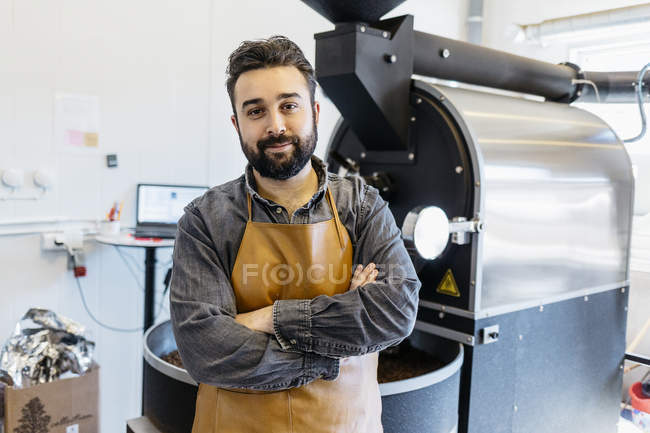 Small business owner with arms crossed at coffee roaster shop — Stock Photo