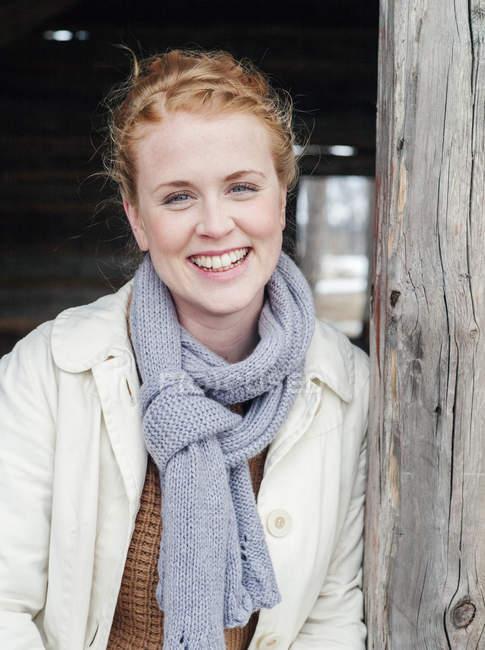 Mujer joven sonriente en cabaña de madera mirando a la cámara - foto de stock