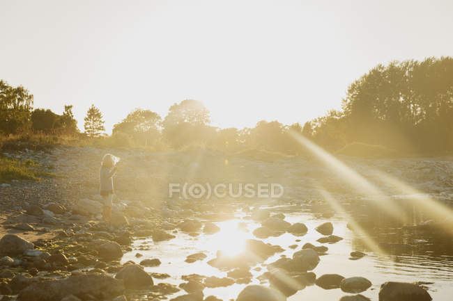 Boy playing on riverbank, lens flare — Stock Photo