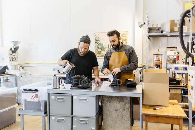 Двоє чоловіків рішень кави на комерційній кухні, селективний фокус — стокове фото