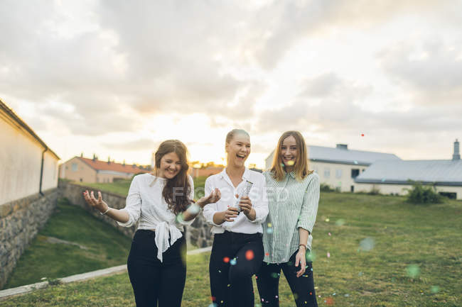 Three young women using confetti cannon outdoors — Stock Photo