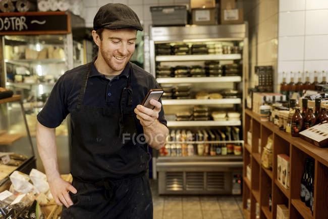 Fishmonger using smart phone in store, selective focus — Stock Photo