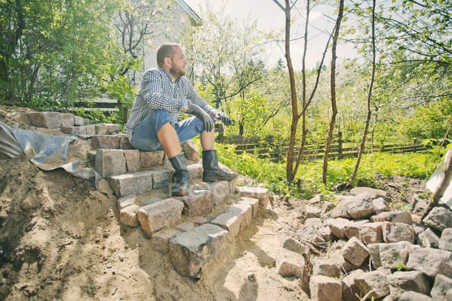 Средний взрослый мужчина отдыхает на незаконченной лестнице в Хейнола, Финляндия — стоковое фото