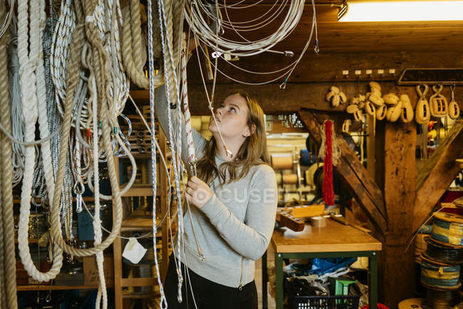 Teenage girl reaching up to touch ropes in rope maker store — Stock Photo