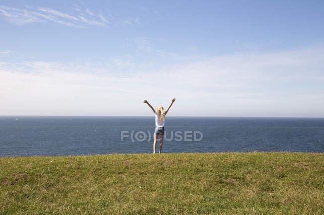 Fille avec les bras levés dans un champ près de la mer à Kaseberga, Suède — Photo de stock