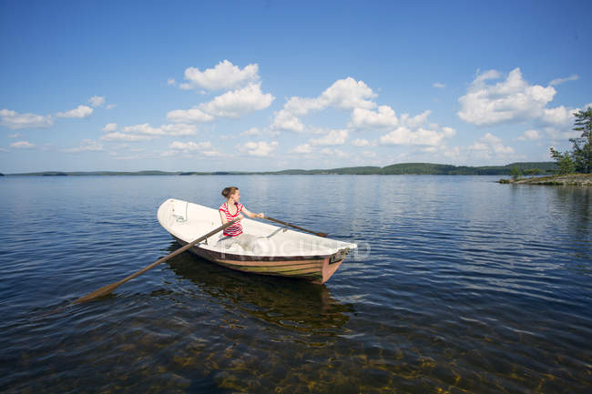 Mid adult woman rowing boat in lake in Finland — Stock Photo