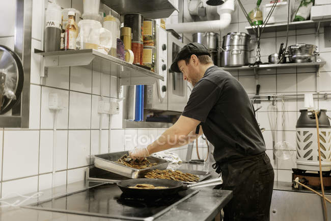 Side view of fishmonger cooking in kitchen, selective focus — Stock Photo