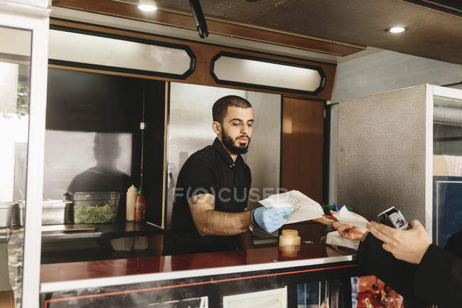 Food truck worker serving customer, selective focus — Stock Photo