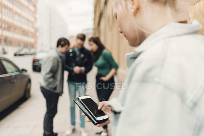 Teenage girl checking cell phone on city street — Stock Photo