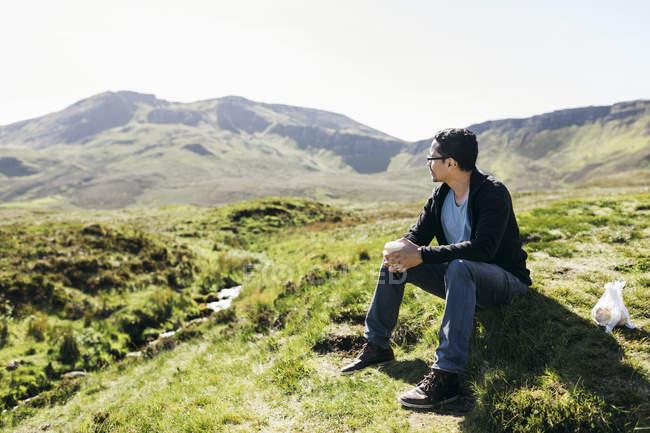 Mann sitzt auf Hügel in inneren Hebriden, Schottland — Stockfoto