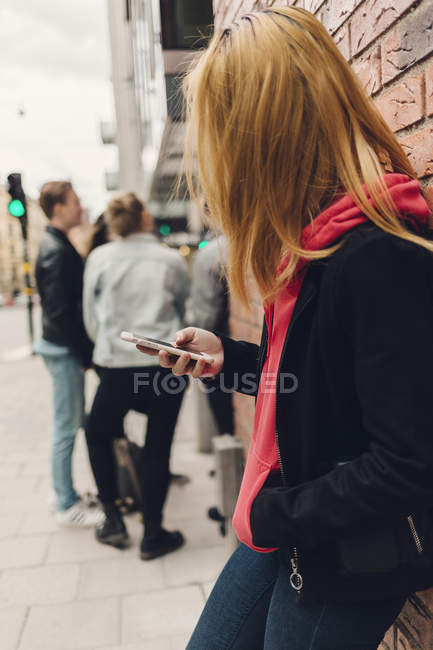 Teenage girl looking at cell phone on city street in Sweden — Stock Photo