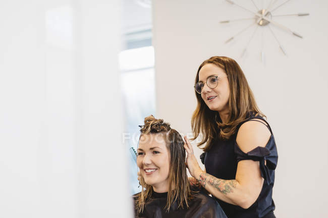 Hairdresser cutting clients hair in salon, selective focus — Stock Photo