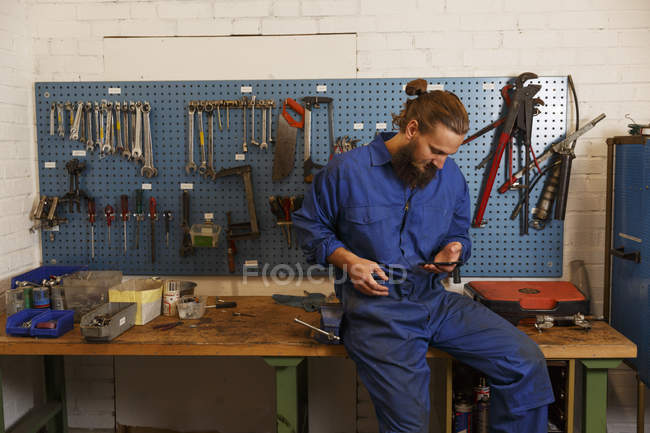 Mechanic checking phone in workshop against tools — стоковое фото