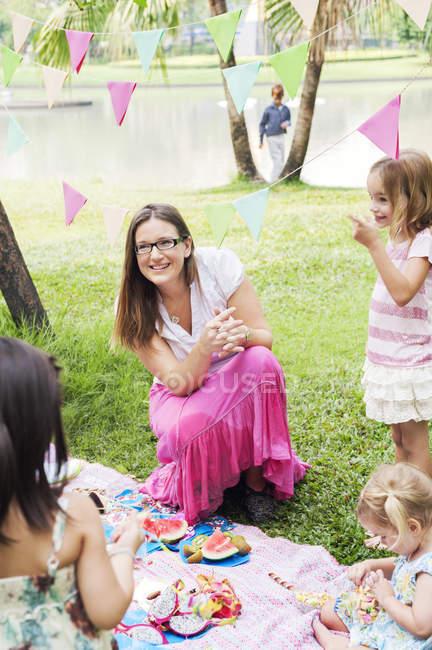 Мати з дітьми в день народження пікніка, Зосередьтеся на передньому плані — стокове фото