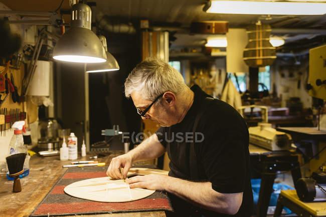 Craftsman working in guitar making workshop, selective focus — Stock Photo