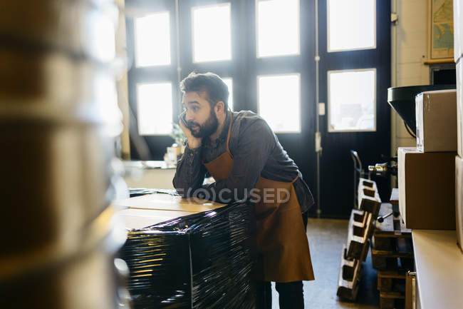 Small business owner at coffee roaster shop talking on smartphone — Stock Photo