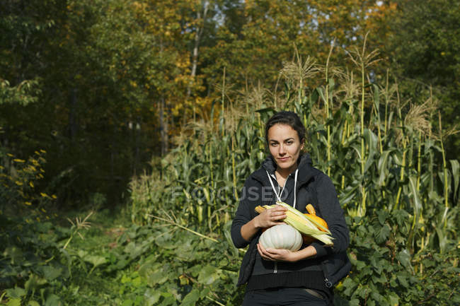 Woman holding freshly picked vegetables, focus on foreground — стоковое фото