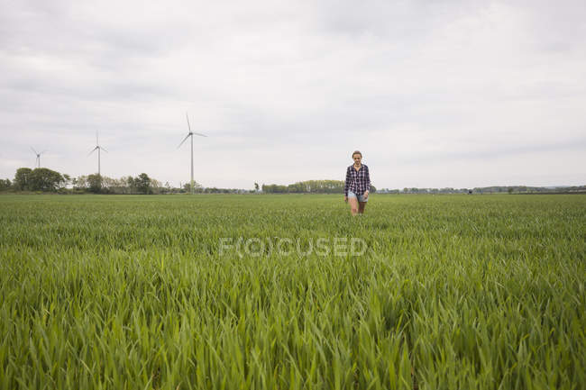 Agricultural worker walking through field under overcast sky — Photo de stock