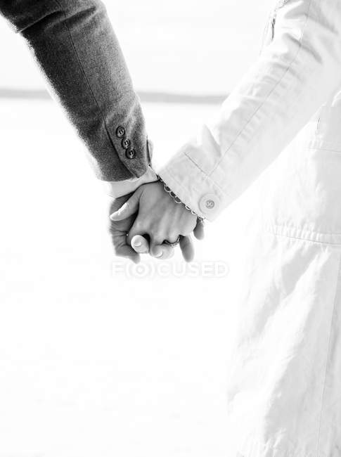 Cropped view of man and woman holding hands, black and white — Stock Photo