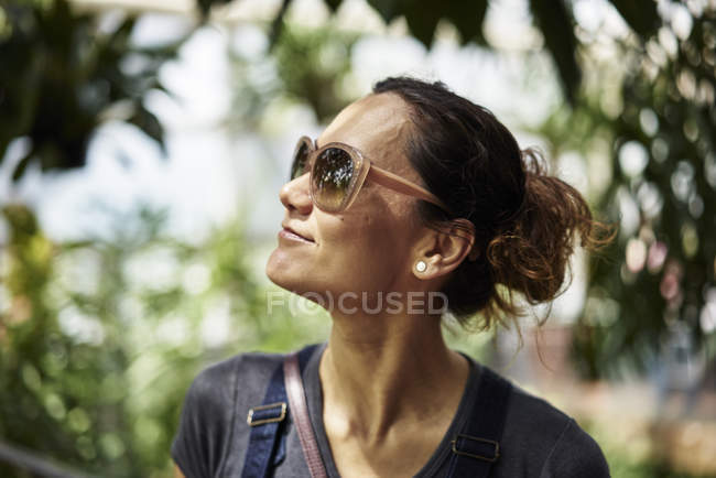 Woman in sunglasses looking away, focus on foreground — Stock Photo