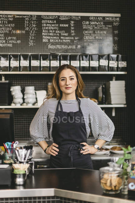 Portrait of barista with hands on hips behind counter in cafe — Stock Photo