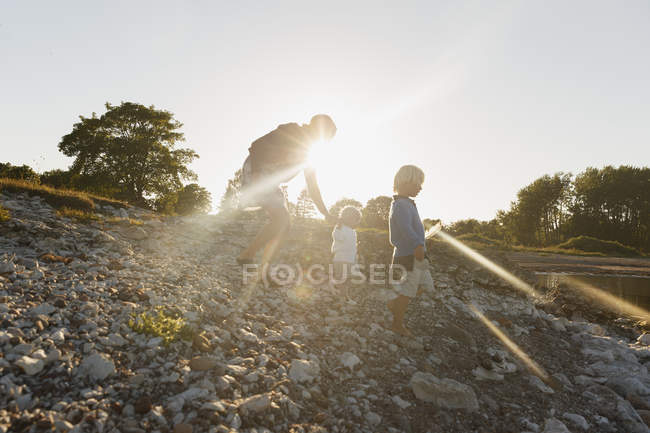 Family on riverbank in Gotland, Sweden, lens flare — Stock Photo