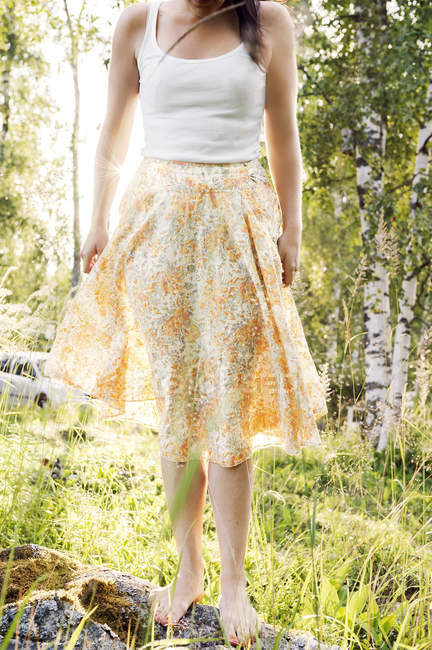 Cropped view of young woman wearing floral skirt outdoors — Stock Photo