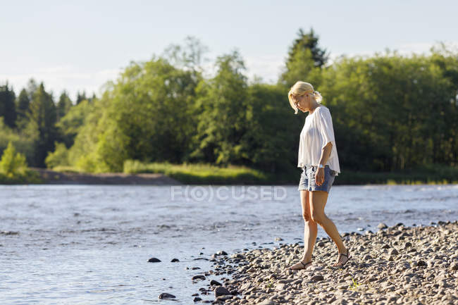 Side view of woman on riverbank, focus on foreground — Stock Photo