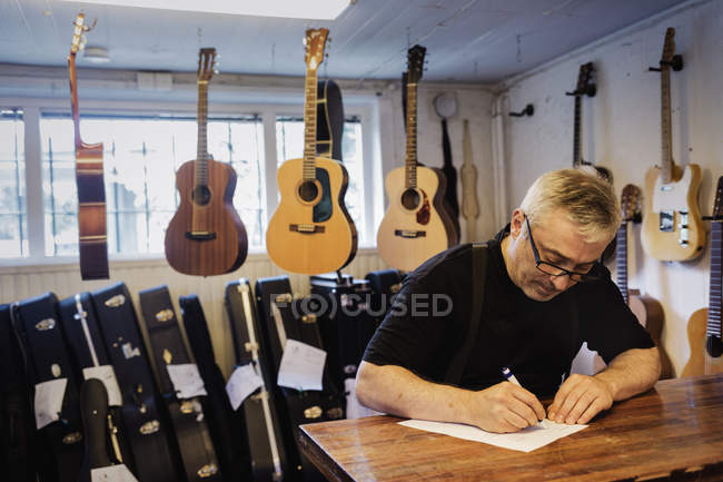 Craftsman writing in guitar making workshop, focus on foreground — Stock Photo